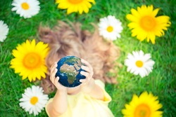 Child holding 3d planet in hands against green spring background. Earth day holiday concept. Elements of this image furnished by NASA