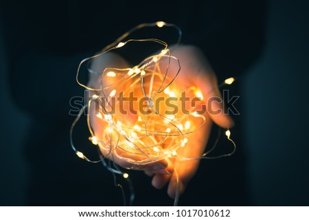 Child holding fairy lights in his hands