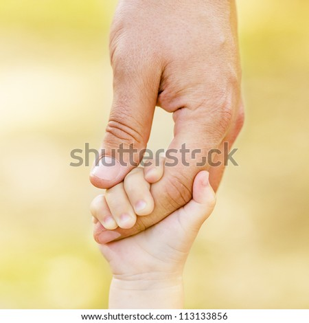 Child holding father's hand - stock photo