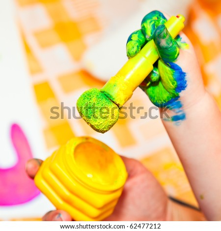 Child holding finger paint brush close-up