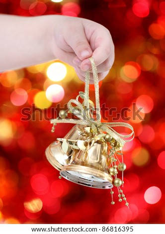 Child holding golden Christmas tree decorations on lights background