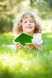 Child holding green grass house in hands. Ecology concept