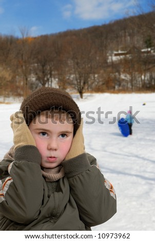 Child holding his ears against the cold