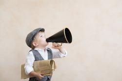 Child holding loudspeaker and newspaper. Kid shouting through vintage megaphone. Business news concept