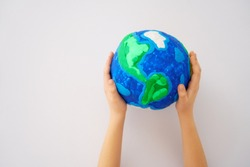 Child holding planet in hands against white background. Earth day holiday concept.