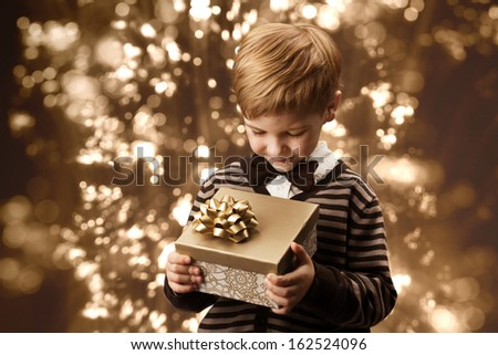 Child holding present gift box. Boy in vintage style smart casual clothing, brown colors.