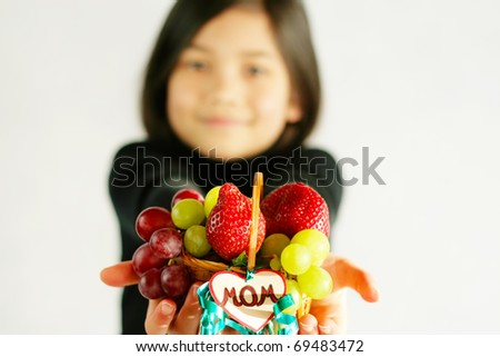 Child holding small fruit basket with a tag for mom