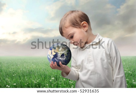 Child holding the earth in his hand with countryside on the background