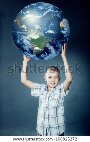 Child holding the earth in his hands on gray background. Elements of this image furnished by NASA.