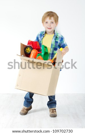 Child holding toys packed in cardboard box. Moving and growing concept