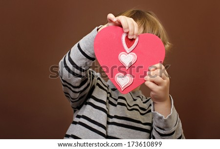 Child holding  Valentine's Day Craft with Heart stickers - stock photo