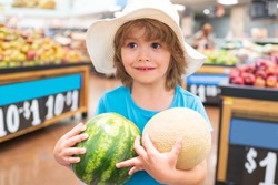 Child holding watermelon in supermarket. Sale, consumerism and kids concept. Vegetables in store