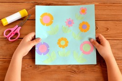Child holds a card with flowers in his hands. Glue, scissors on a wooden table. Paper flower craft for kids. Child art project.