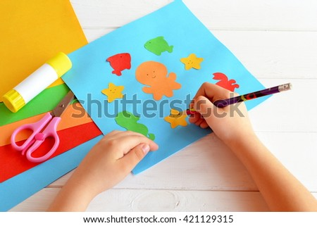 Child holds a pencil and draws. Child doing a card with sea animals and fish. Sheets of colored paper, scissors, glue, set for kids art