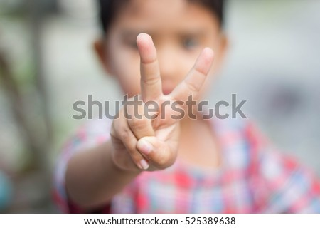 Child holds two fingers up