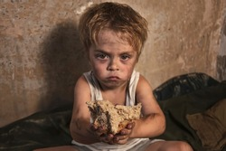 Child homeless, beggar holds a piece of black bread (concept of war, poverty, crisis). Focus on bread.