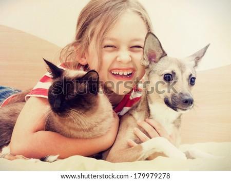 child hugging a cat and dog  ストックフォト ©