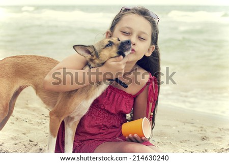 child hugging a puppy on the beach