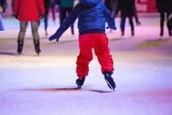 Child ice skating at night in Vienna, Austria. Winter.