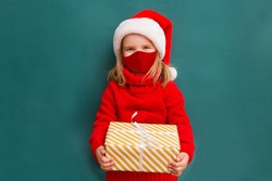 Child in a red sweater and a Santa hat wearing medical face mask with Christmas gift box. Christmas shopping.  Copy space.