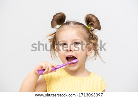 child in a yellow T-shirt with clean teeth brushing on a light background Foto stock ©