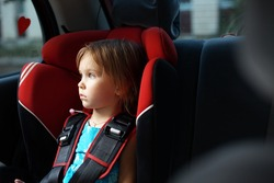 Child in auto baby seat in car looking at window