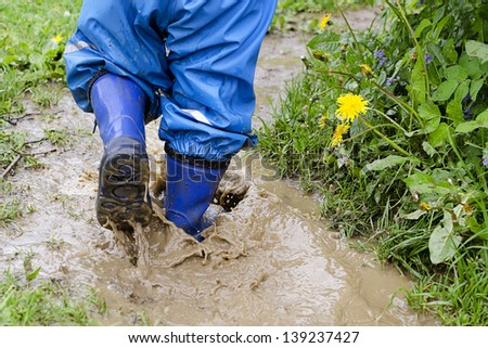 Child in boots walking and jumping in muddy puddle after rain.