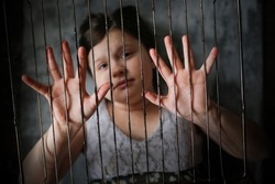 child in cage, concept of restriction of freedom and violation of rights of child, quarantine and a child locked in 4 walls. Child and metal grill, childhood safety