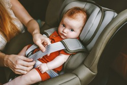 Child in car mother putting baby in safety car seat family road trip vacations lifestyle child care transportation rear-facing