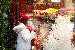 Child in face mask at store window on traditional Christmas market in coronavirus outbreak. Covid-19 pandemic. Safe Xmas shopping, gifts and presents with kids on snowy winter day.