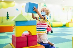 Child in face mask playing with colorful construction toy blocks. Preschool and kindergarten kids in covid-19 pandemic. Safety measures to prevent coronavirus spread. Educational toys in playroom.