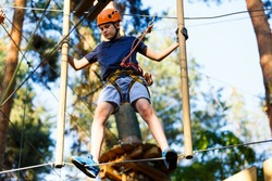 Child in forest adventure park. Kid in orange helmet  and blue t shirt climbs on high rope trail. Agility skills and climbing outdoor amusement center for children. young boy plays outdoors.