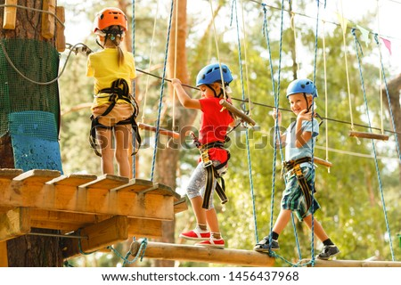 Child in forest adventure park. Kids climb on high rope trail. climbing outdoor amusement center for children. Little girl playing outdoors. School yard playground with rope way.