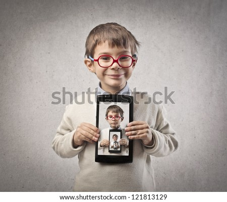 Child, in front of a mirror, with a tablet