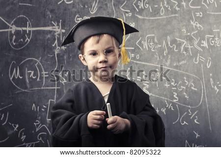Child in grad uniform with blackboard in the background