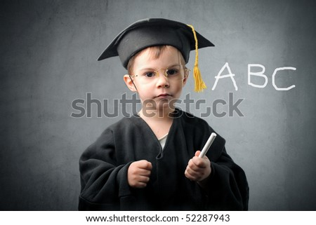 Child in graduate uniform writing some letters