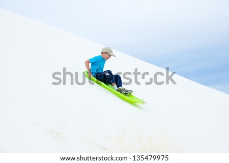 Child in green sled rolls with sand dunes .. White Sands National Monument, New Mexico