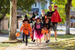 Child in Halloween costume. Mixed race Asian and Caucasian kids and parents trick or treat on street. Little boy and girl with pumpkin lantern and candy bucket. Baby in witch hat. Autumn holiday fun.