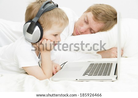 child in headsets with computer while father is asleep, family leisure