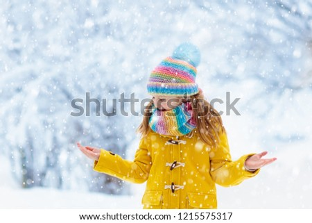 Child in knitted hat playing in snow on Christmas vacation. Winter outdoor fun. Knitting and outerwear for family. Kids play in snowy park. Little girl in knit scarf and mittens catching snowflakes. #1215575317