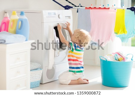 Child in laundry room with washing machine or tumble dryer. Kid helping with family chores. Modern household devices and washing detergent in white sunny home. Clean washed clothes on drying rack.  #1359000872