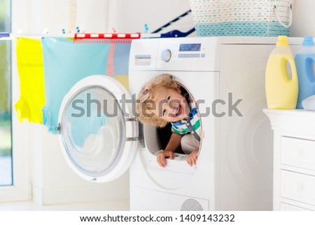 Child in laundry room with washing machine or tumble dryer. Kid helping with family chores. Modern household devices and washing detergent in white sunny home. Clean washed clothes on drying rack.  #1409143232