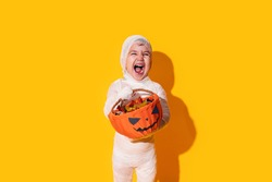 Child in mummy costume holding basket of chocolates in front of yellow background.
