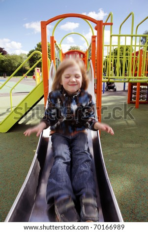 child in playground. kid in action at speed on slide. boy play on leisure equipment
