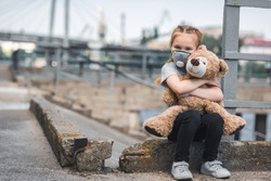 child in protective mask hugging teddy bear on street, air pollution concept