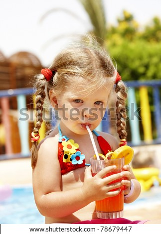 Child in  red bikini drinking through  straw  juice.
