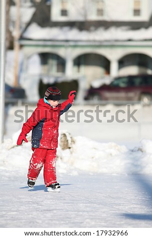 child in red ice skating in outdoor ice rink