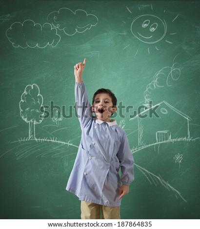 Child in school against a green blackboard