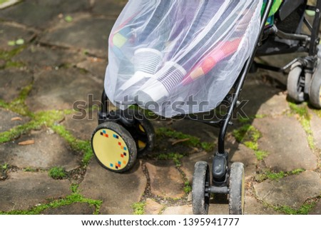 Child in stroller covered with protective net during walk. Baby carriage with anti-mosquito white cover. Midge protection for children during outdoor walking season #1395941777
