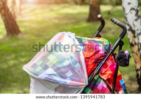 Child in stroller covered with protective net during walk. Baby carriage with anti-mosquito white cover. Midge protection for children during outdoor walking season #1395941783